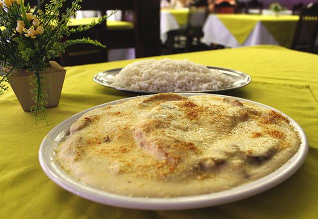 Peixe à Delícia de Sirigado serve 2 pessoas: Filé de Sirigado, banana frita, gratinado com queijo parmesão, acompanha arroz branco de R$65 por R$44,90